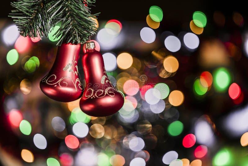 Choinek czerwone dzwonkowe dekoracje przeciw ładnemu bokeh tłu fotografia stock