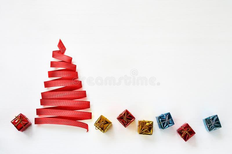 Choinka robić od czerwonego faborku z małymi prezentami na bielu obrazy stock