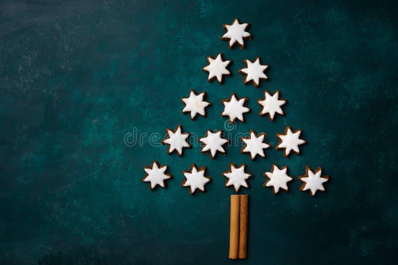 Choinka robić od Niemieckiej tradycyjnej wakacje gwiazdy kształtował cynamonowych ciastka niebieska tła ciemnej nieskończoności i zdjęcia stock