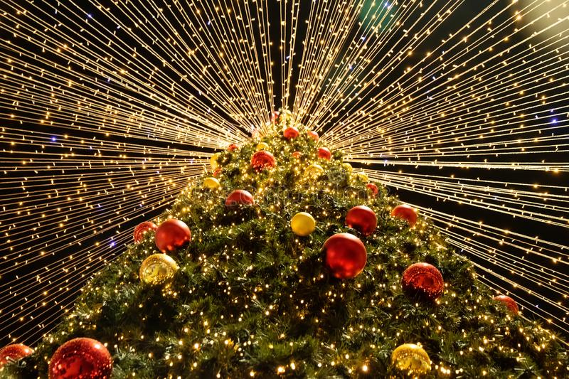 Choinka z barwionymi piłkami i jarzyć się światłami nowy rok, obrazy stock