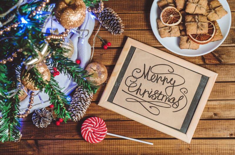 Choinka, zabawki, prezenty i karta która mówi ` Wesoło bożych narodzeń `, fotografia stock