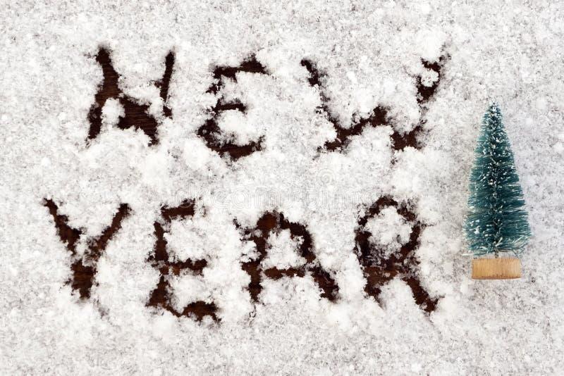 Choinki pamiątka obok wpisowego nowego roku na białym śniegu Tło dla projekta karty na temacie zdjęcie royalty free