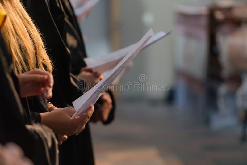 Choir i cantanti che tengono il punteggio musicale e che cantano sul gradu dello studente fotografia stock