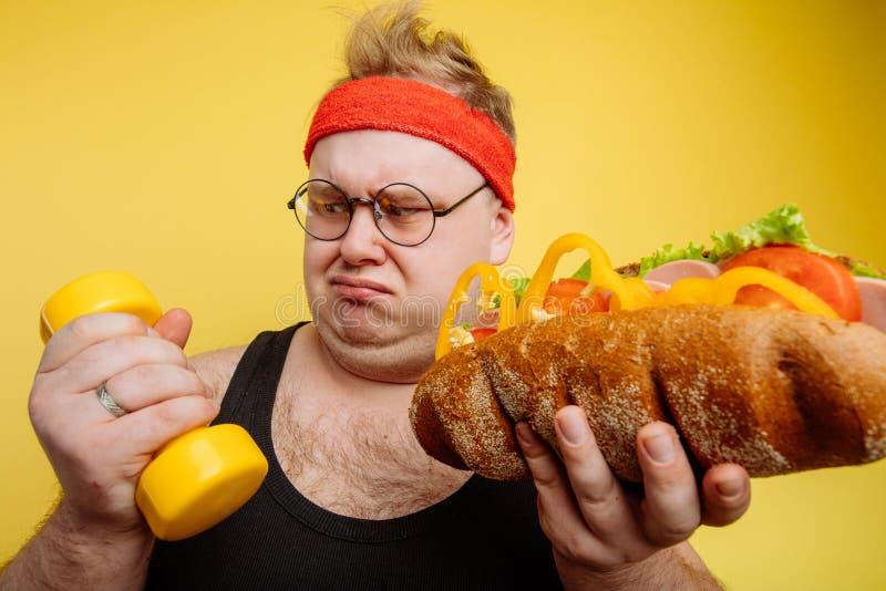 Choise grasso dell'uomo fra lo sport ed il pasto rapido fotografia stock libera da diritti