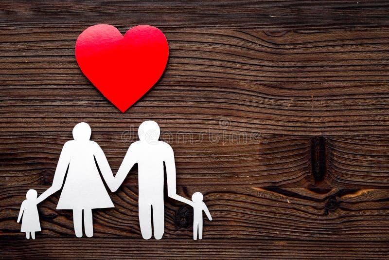 Choisissez l'assurance médicale maladie de famille Coeur et silhouette de papier de famille sur le copyspace en bois foncé de vue photo libre de droits