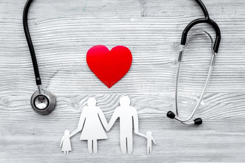 Choisissez l'assurance médicale maladie Stéthoscope, coeur de papier et silhouette de famille sur la vue supérieure de fond en bo photographie stock