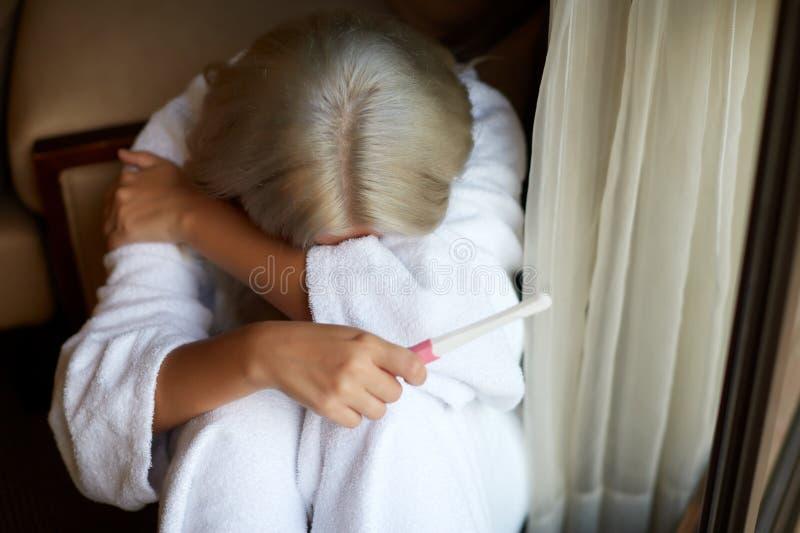 Choisissez la femme triste se plaignant en tenant un essai de grossesse se reposant sur un divan dans le salon à la maison images stock