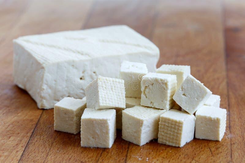 Choisissez le bloc de tofu blanc avec les cubes coupés en tofu sur le choppin en bois photos libres de droits