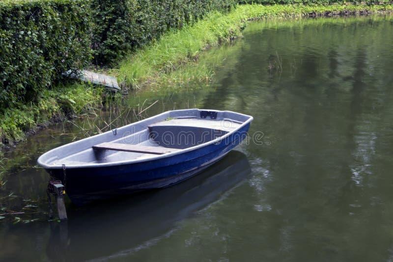 Choisissez le vieux bateau bleu vide amarré dans les bosquets verts photo libre de droits