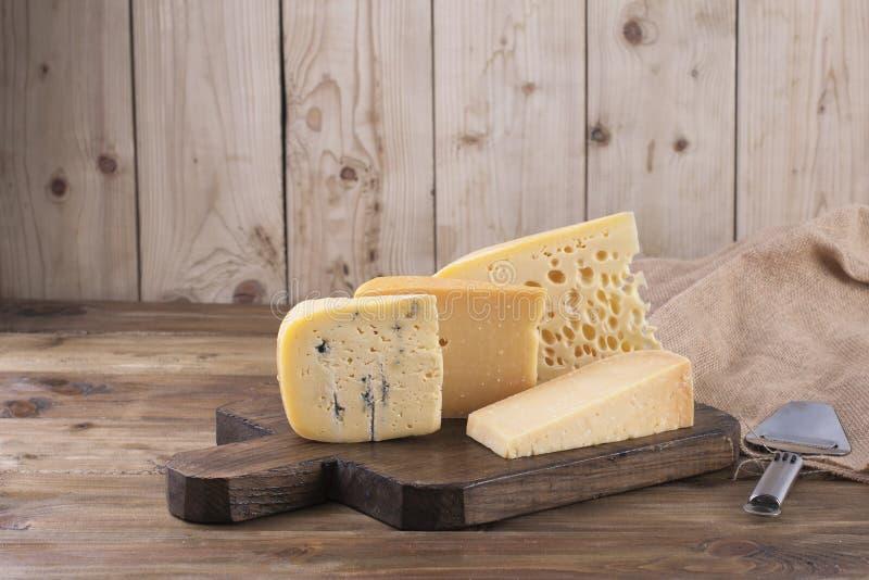 Choix classique de fromage différent, sur un vieux conseil en bois, couteau de fromage et tissu photographie stock