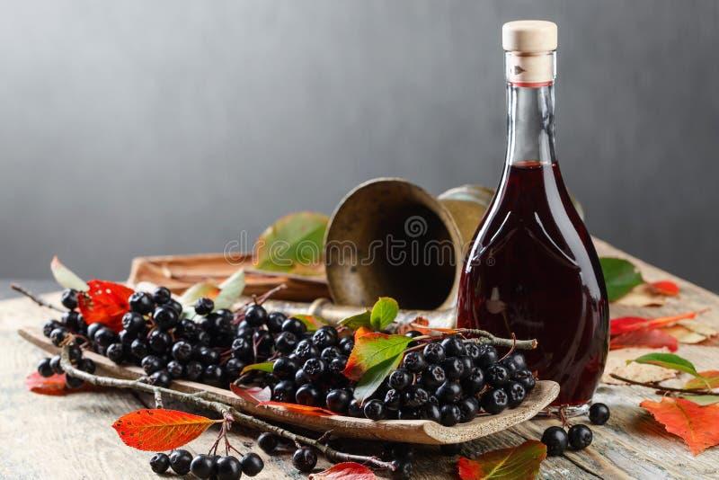 Chokeberry et bouteille noirs avec du jus images libres de droits