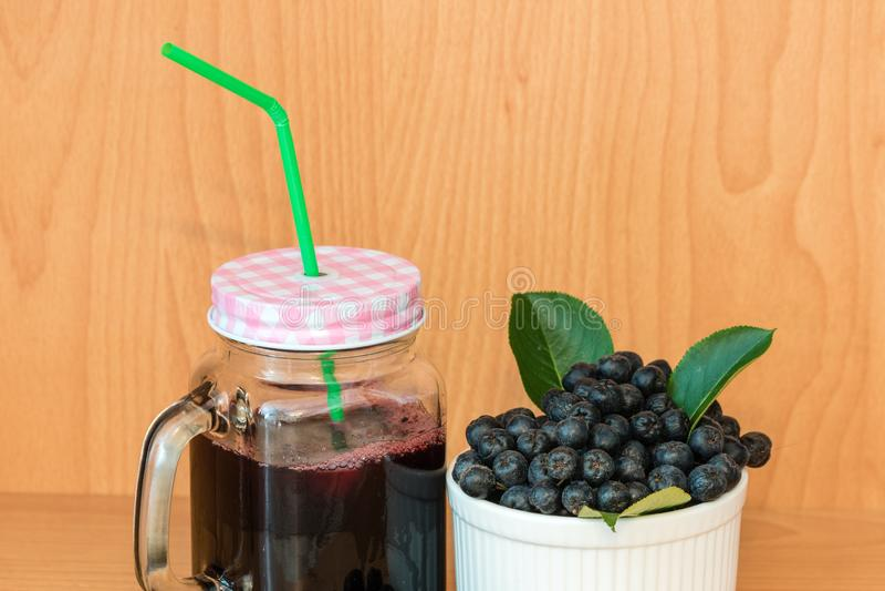 Chokeberry oder Aronia-melanocarpa Saft mit Eis im Glas mit Stroh und Beere im Korb lizenzfreie stockbilder