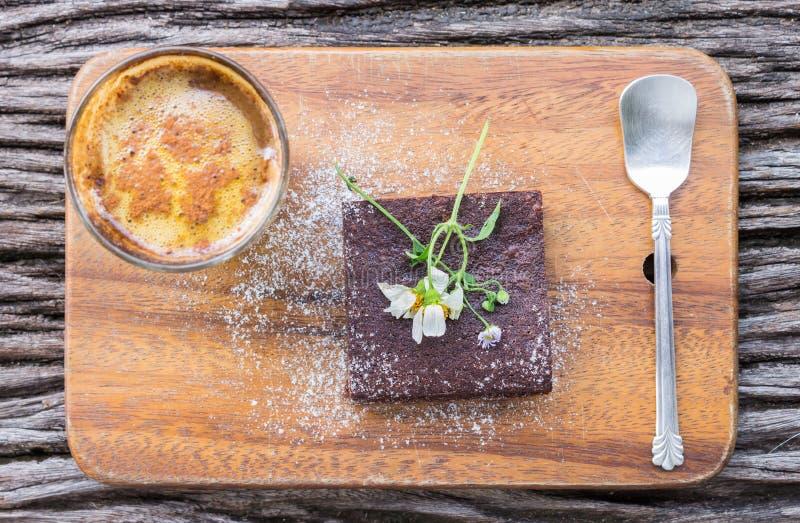 Choklad Brownie Cake och kaffe och tusensköna på skärbräda på royaltyfria bilder