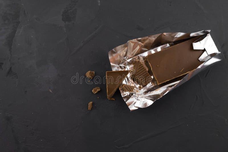 Choklad, i att f?rpacka f?r folie Lappa av choklad Stranda av h?r v?nder mot in royaltyfria bilder