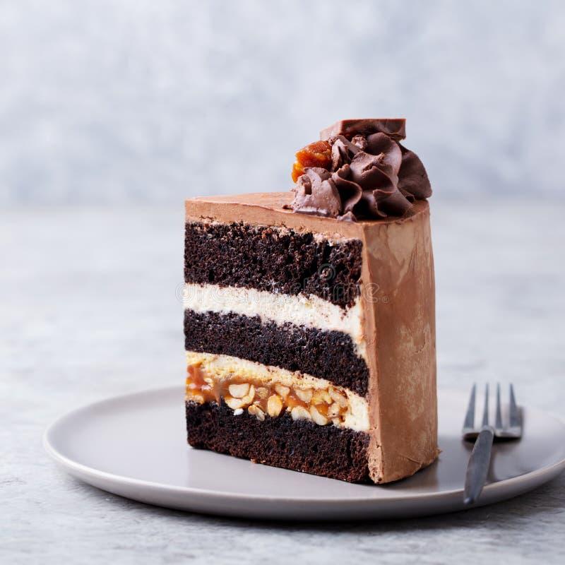 Choklad karamell, jordnötkaka, flinar på en platta Gr? f?rgbakgrund close upp royaltyfri fotografi