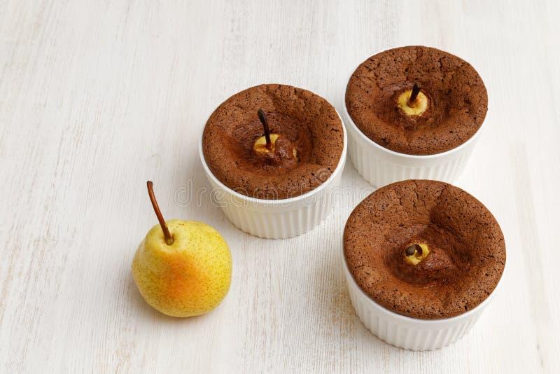 Choklad-mandel efterrätt med päron i den vita keramiska bakningmaträtten arkivbild
