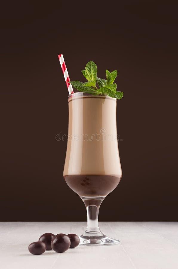 Choklad mjölkar coctailen i bägare med den nya gröna mintkaramellen, rött sugrör och godisar i den eleganta mörka bruna stånginre royaltyfri foto