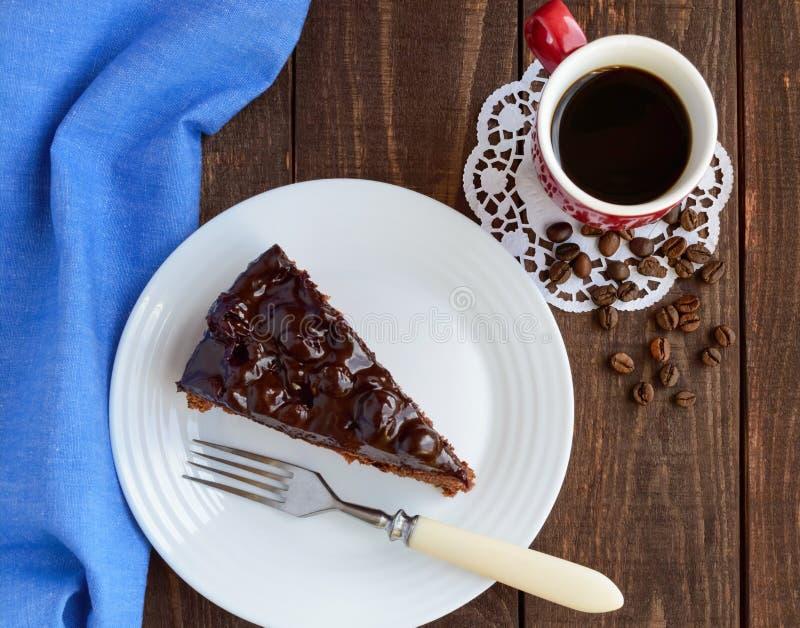 Choklad- och Cherrycake Ett stycke på en vit platta arkivfoto