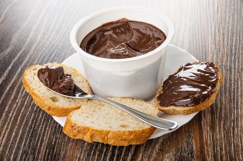 Choklad smältte ost i sked på bröd, smörgås med smältt ost, krus med smältt ost i platta på tabellen arkivbild