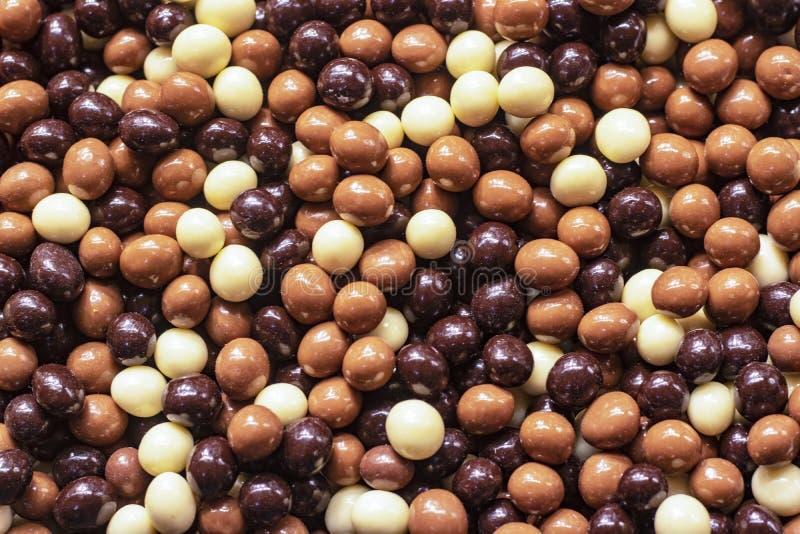 Choklad täckte muttrar i olika färger royaltyfri fotografi
