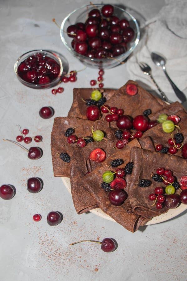 Choklad tunna runda pannkakor som kläs med körsbärsrött driftstopp arkivbilder