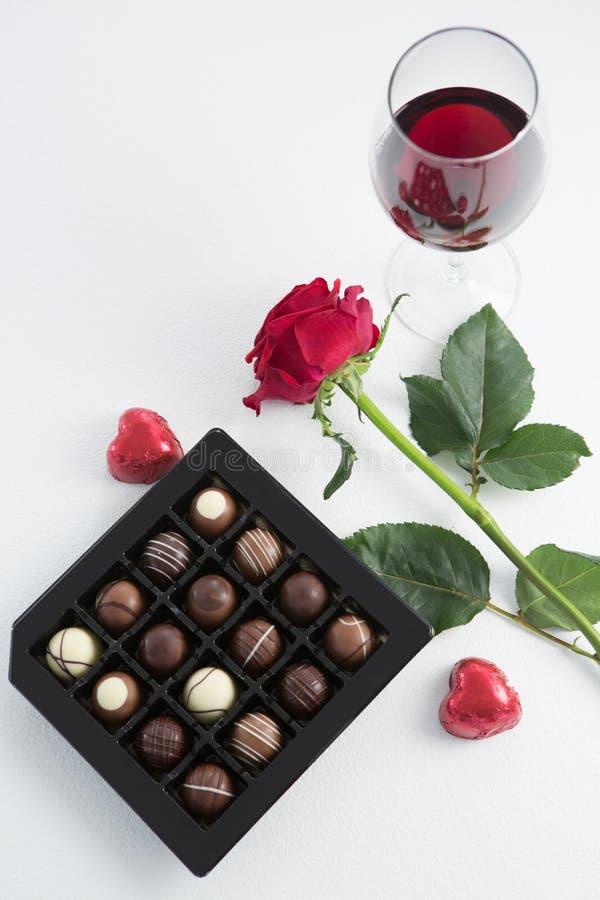 Chokladask, rosor och rött vinexponeringsglas på vit bakgrund arkivfoto