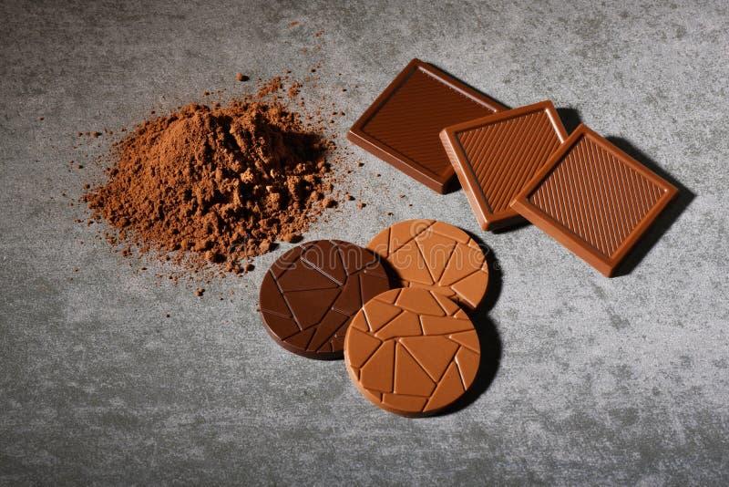 Chokladbegrepp, grupp av cirkeln och fyrkantigt formmörker och att mjölka chokladstycken med kakaopulver royaltyfri fotografi