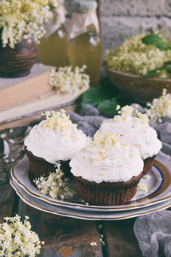 Chokladcapcakes med vaniljkräm som strilas med vita choklad- och fläderbärblommor tappning för stil för illustrationlilja röd kop fotografering för bildbyråer