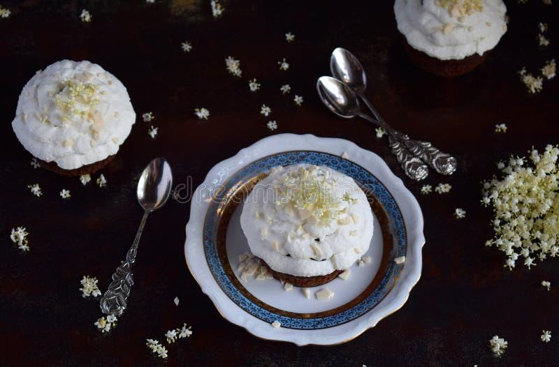 Chokladcapcakes med vaniljkräm som strilas med vita choklad- och fläderbärblommor tappning för stil för illustrationlilja röd kop arkivfoton
