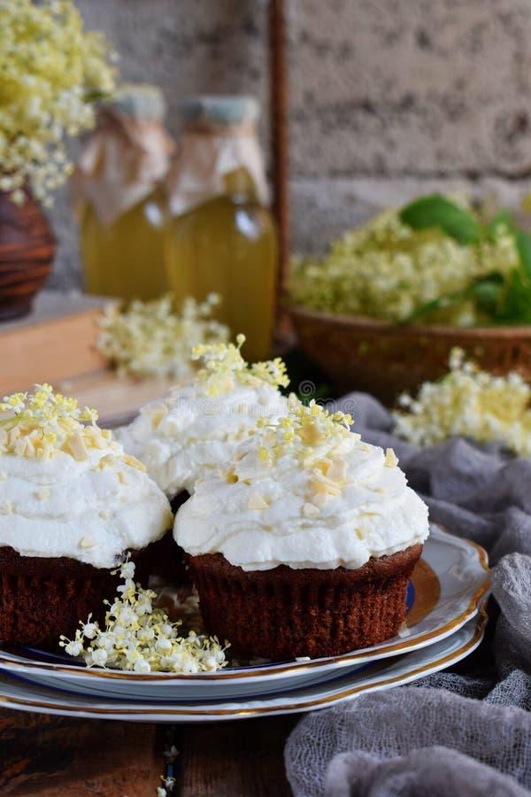 Chokladcapcakes med vaniljkr?m som strilas med vita choklad- och fl?derb?rblommor tappning f?r stil f?r illustrationlilja r?d kop arkivfoton