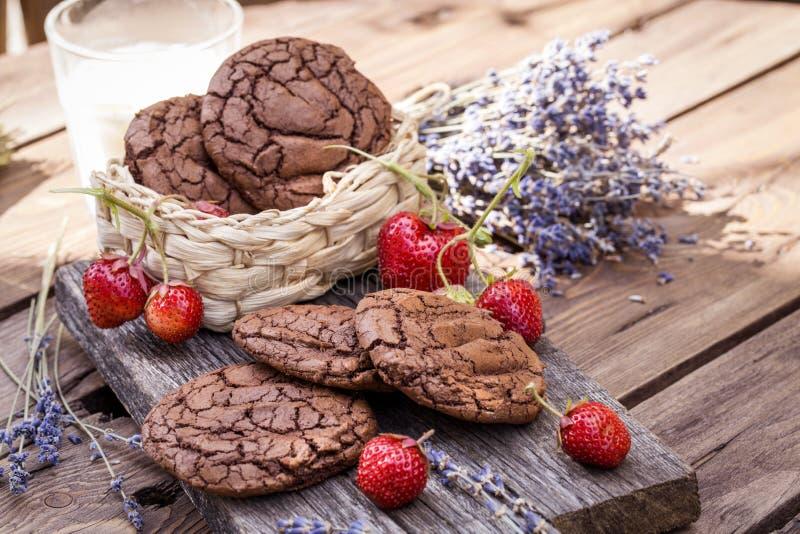 Choklade kakor med nya jordgubbar på träbakgrund arkivbilder