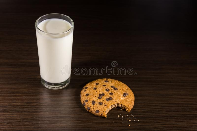 Choklade kakor och exponeringsglas av mj?lkar p? tr?tabellen arkivbilder