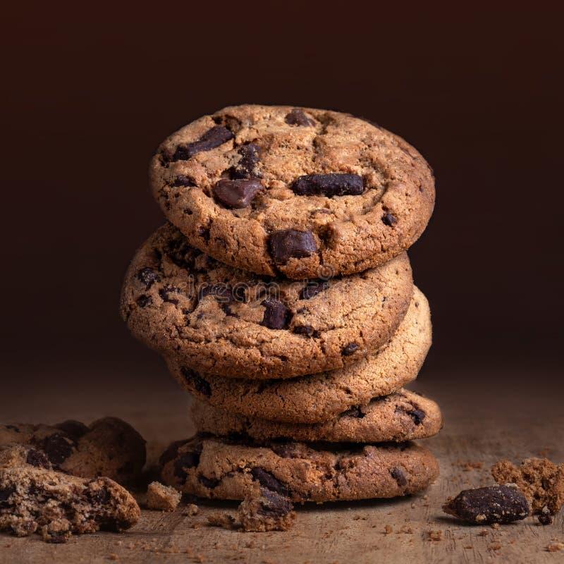 Choklade kakor på den gamla trätabellen Staplade chokladkakor på mörk bakgrund, closeup arkivfoto