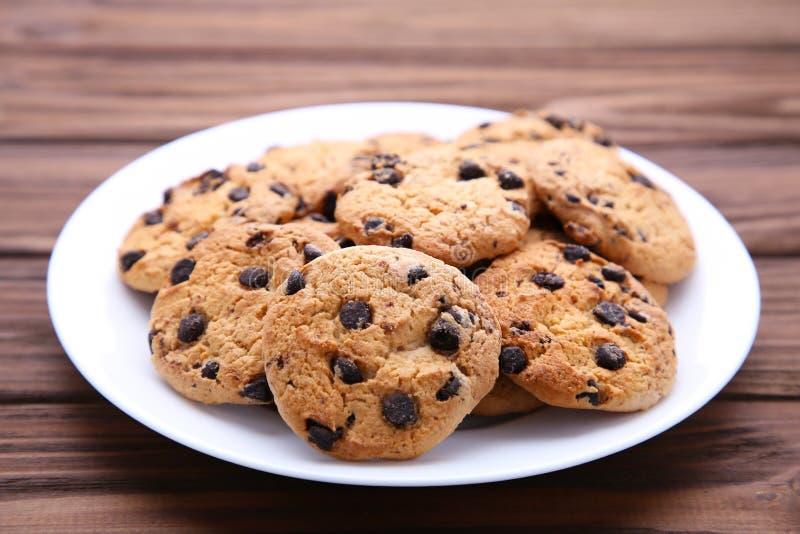 Choklade kakor på plattan på brun träbakgrund royaltyfria bilder