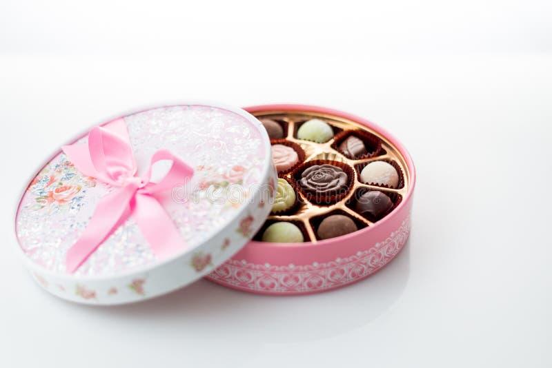 Choklader i rosa färgask på vit bakgrund royaltyfri foto