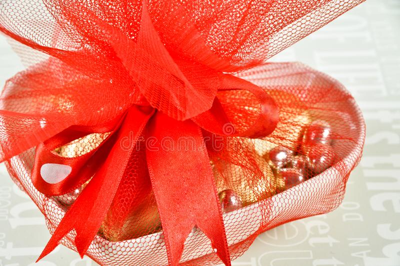 Choklader som slås in i kulöra folier som packas med det röda bandet royaltyfri fotografi