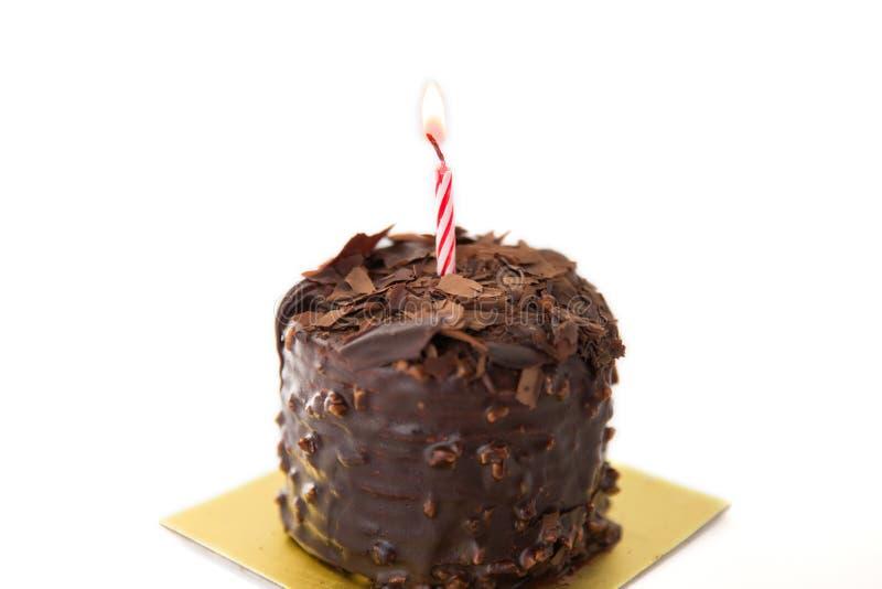 Chokladfödelsedagkaka på vit bakgrund arkivfoton