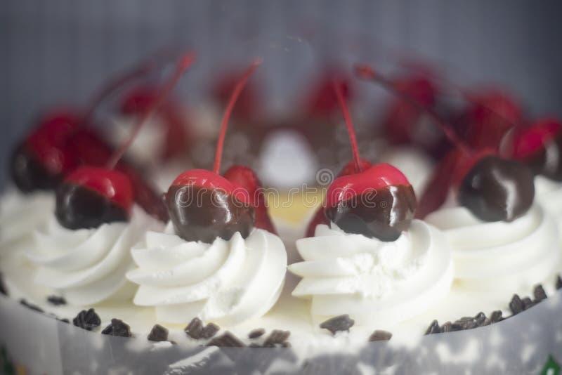 Chokladfondue med Cheery-frukt i jultemat som toppar över att pipa krämen på tårtan arkivfoto