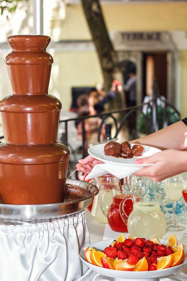 Chokladfondue med fruktsortimentet Kvinnlig hand som doppar jordgubben på en steknål in i den varma springbrunnen för chokladfond fotografering för bildbyråer