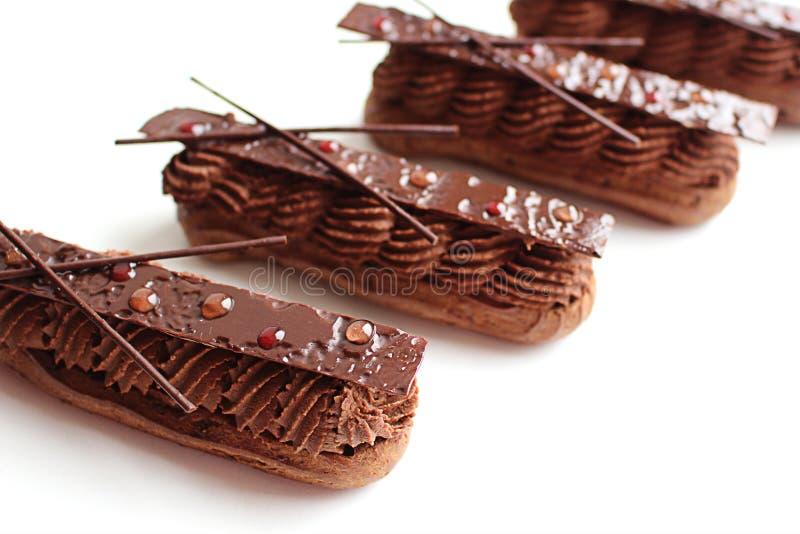 Chokladganacheeclairs med skinande chokladgarneringar royaltyfria bilder