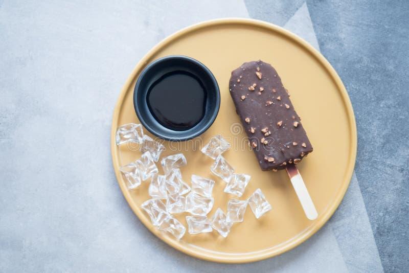 Chokladglassst?ng med muttrar p? den gula plattan royaltyfria foton