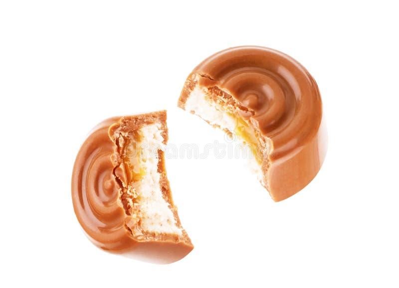 Chokladgodisar i ett snitt med karamell på en vit bakgrund arkivfoto