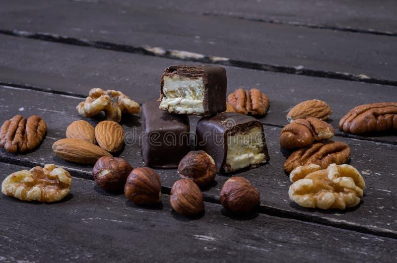 Chokladgodisar och muttrar på en trätabell royaltyfria bilder