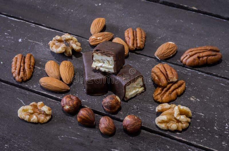 Chokladgodisar och muttrar på en trätabell arkivbild