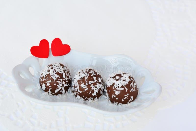 Chokladgodisen med kokosnöten flagar med röda hjärtor royaltyfria foton