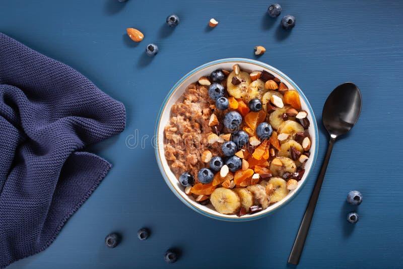 Chokladhavremjölhavregröt med blåbäret, muttrar, banan, torkad aprikos för bästa sikt för sund frukost royaltyfri bild