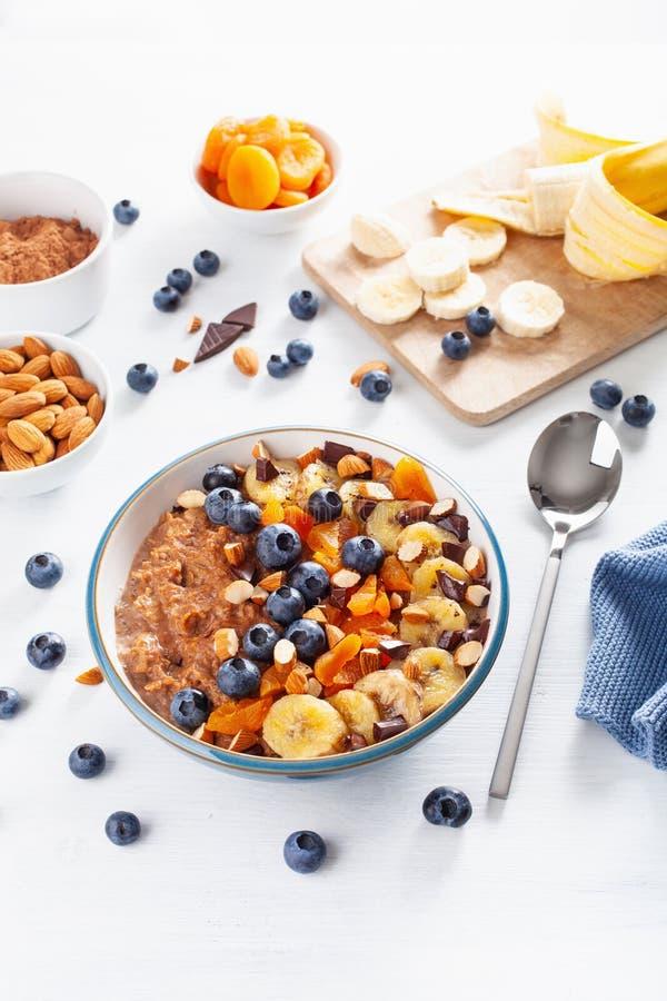 Chokladhavremjölhavregröt med blåbäret, muttrar, banan, torkad aprikos för sund frukost royaltyfri bild