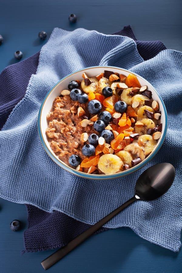 Chokladhavremjölhavregröt med blåbäret, muttrar, banan, torkad aprikos för sund frukost arkivbilder