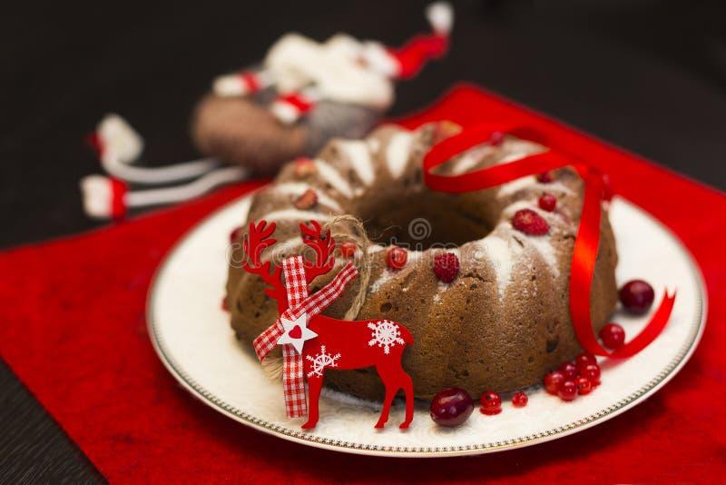 Chokladkaka för jul eller för nytt år med pudrat socker på överkanten, nya röda bär på den vita porslinplattan fotografering för bildbyråer