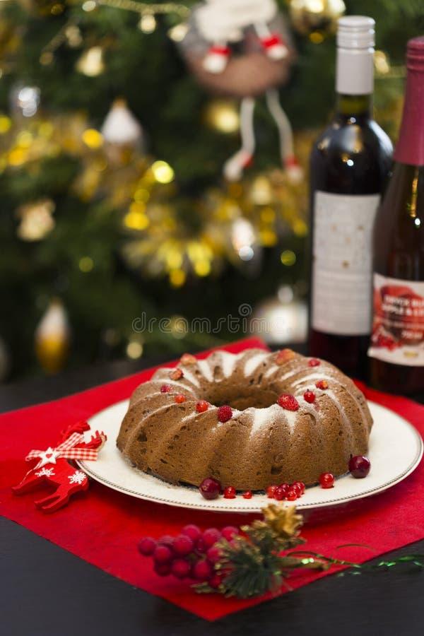 Chokladkaka för jul eller för nytt år med pudrat socker på överkanten, nya röda bär på den vita porslinplattan royaltyfri bild